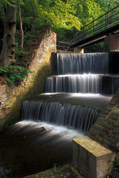 WAL: Northern Region, Flintshire County, Clwydian Hills, Holywell, Greenfields Valley Heritage Park, Water cascades over a mill pond's brick weir, in these ruins from an 18th C. copper rolling plant, now in a forest. [Ask for #246.071.]