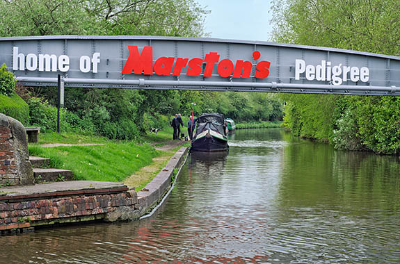 ENG: West Midlands Region, Staffordshire, The Trent Valley, Burton-on-Trent, The Trent and Mersey Canal, Industrial continuity; the canal port responsible for the Marstons and Bass brewery sites of the 1850s is still in use, overpassed by a Marstons pipeline [Ask for #270.247.]